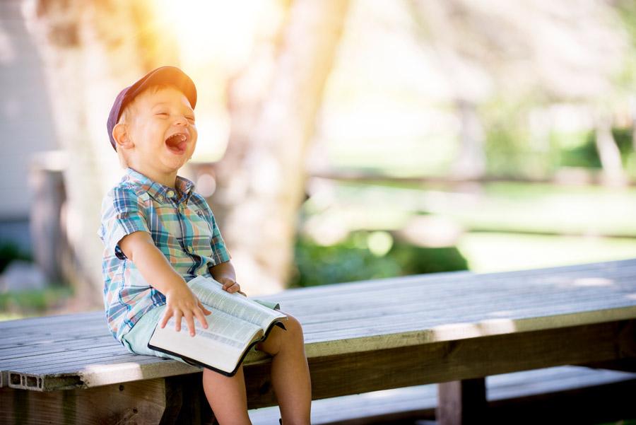 フリー写真 本を開いて笑っている外国の男の子